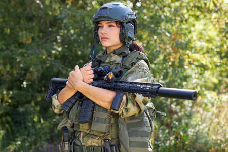 brave caucasian woman is engaged in hunting weapon gun or rifle, wearing military suit. target shot. female hunter in wild forest, nature. successful hunt. hunting sport concept