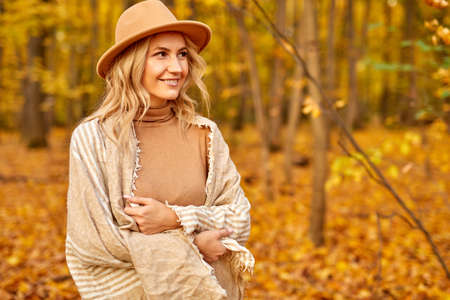 fashionable pretty woman walking outdoors in autumn spring park or forest, she contemplates everything around, wearing warm clothes and hat