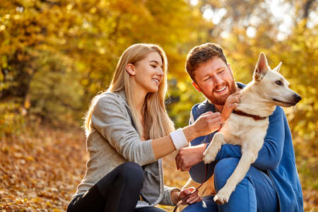 couple dressed casual hugging and taking a walk in nature with their lovely nice dog , autumn season Stockfoto