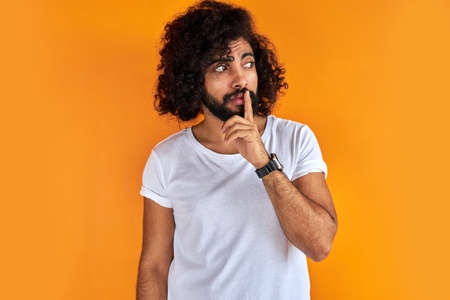 young arab man with curly black hair raising his finger on the front of his mouth asking to be quiet, isolated on orange background, he is looking away