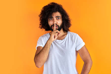 indian arabic male asking to be quiet with finger on lips, silence and secret concept. handsome guy keep silence, isolated over orange background
