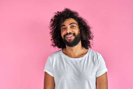 pleasant indian arabian male in shirt looking at camera, has friendly look, open-minded guy isolated over pink background