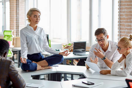 leader of company sits in yoga pose, business woman in formal wear sits with crossed legs in lotus pose, concentrated on thoughts, take break while diverse people working, discussing Stockfoto