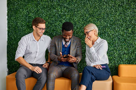 three diverse colleagues sit talking having fun apart form work, laugh looking videos on smartphone