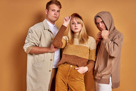 photogenic group of young people posing in stylish cozy outfit, studio shoot. good-looking youth look at camera, stand together, pastel brown background