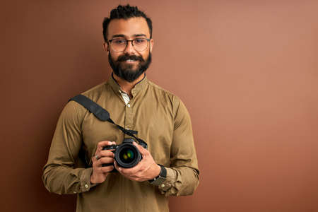 arab man taking photo on camera, holding professional camera in hands, wearing shirt. posing. creativity and photography concept