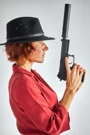 female with weapon against white background, isolated. detective redhead woman in black hat looking away, applying the weapons barrel up