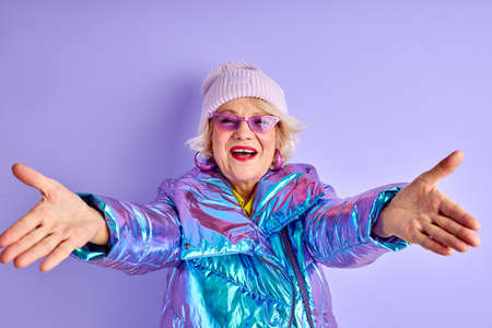 cheerful elderly woman with spread arms look at camera, going to hug, wearing winter coat hat and sunglasses