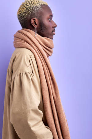 side view on brutal confident african man in trendy wear isolated in studio with purple background, fashionable guy posing, looking away. profile portrait