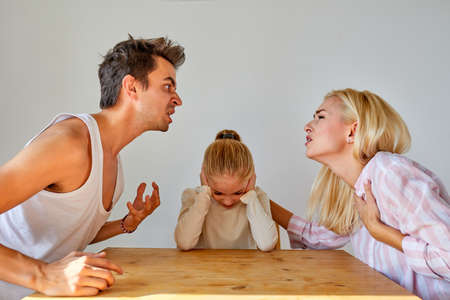 daughter is tired of family conflicts,divorce and children concept. little kid girl is upset with quarrelling of parents, they are going to be divorced