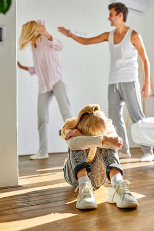 child is tired of family conflicts,divorce and children concept. little kid girl is upset with quarrelling of parents, they are going to be divorced