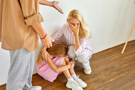 blond woman and child girl sits suffering from cruelty of father, abusive relationships concept, man is screaming and punishing members of family