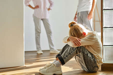 child girl is tired of family conflicts,divorce and children concept. little kid girl is upset with quarrelling of parents, they are going to be divorced