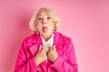 senior woman having fun at free time leisure, showing tongue at camera, crazy woman in pink stylish coat isolated on pink background