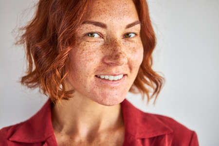natural redhead woman with freckles posing at camera isolated in studio, natural beauty, people and lifestyle concept