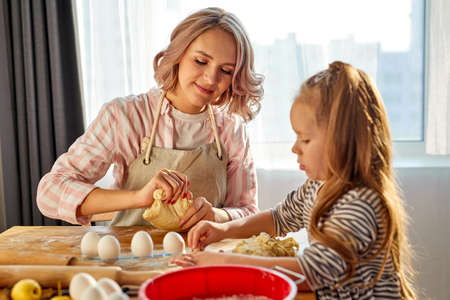 girl learning helping mom in kitchen, happy cute kid daughter and parent mum having fun prepare cookie biscuit cooking together at home Banque d'images