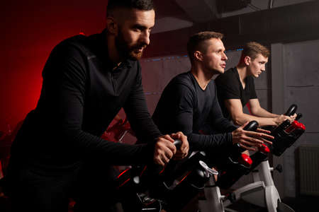 people exercising with bicycles in a gym, training on machine looking forward, wearing black tracksuit 版權商用圖片