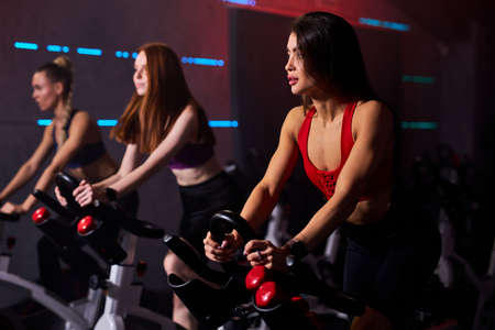 fit women at the gym riding on spinning bike in modern gym. healthy lifestyle and sport concepts
