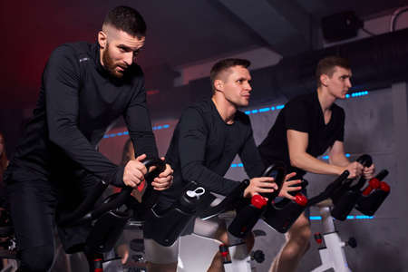 three fitness men riding exercise bikes in gym, they lead healthy lifestyle, have intensive training