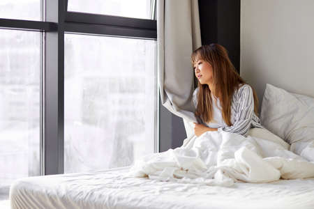 asian woman sits on bed looking outside through window, sits in contemplation, thinking. in bedroom, wearing pajamas Banque d'images