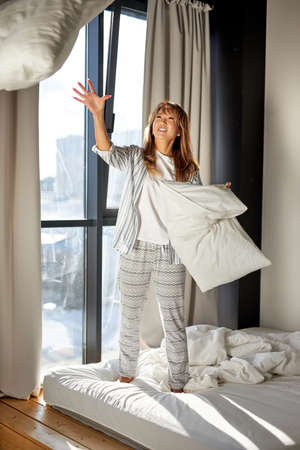 asian woman play with pillows in the morning, happy to have rest, enjo weekends alone, cheerful woman in pajamas stands on bed