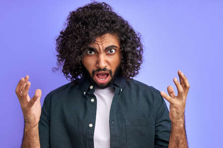 disgruntled curly male shout, spread arms, he is irritated by news or someones behavior, isolated on purple background