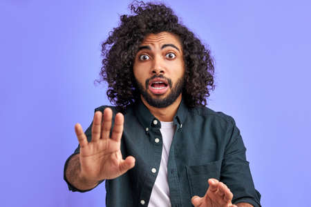 alarming scared panicking man is gesturing stop, afraid of something. arabic young male with long curly hair afraid and terrified with fear expression