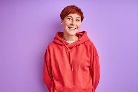 woman in red pullover stand smiling isolated over purple background, portrait