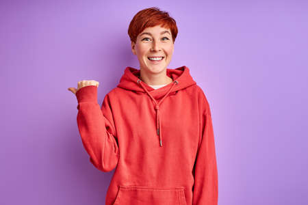 redhead woman showing at side, pointing finger and smiling, isolated on purple background Archivio Fotografico