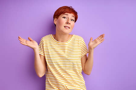 woman shrugging, i dont know. woman is misunderstanding , have doubts isolated on purple