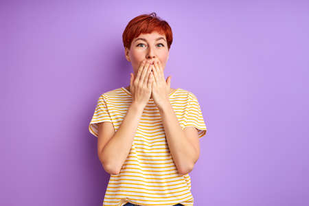 redhead woman stand closing mouth, in shock. isolated over purple background