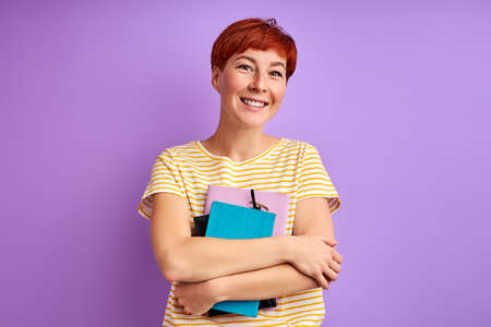 woman holds books in hands and posing at camera, isolated over purple background. young redhead female enjoy studying, education