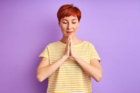 calm female with natural red short hair meditating, praying with eyes closed, isolated Archivio Fotografico