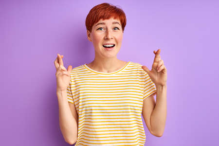 redhead adult woman hope for the best, keeping fingers together, good luck. isolated over purple background Archivio Fotografico