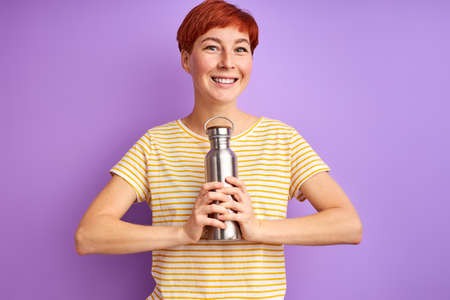 woman with thermos isolated on purple background, young female in casual wear shine with happiness, smile at camera Archivio Fotografico