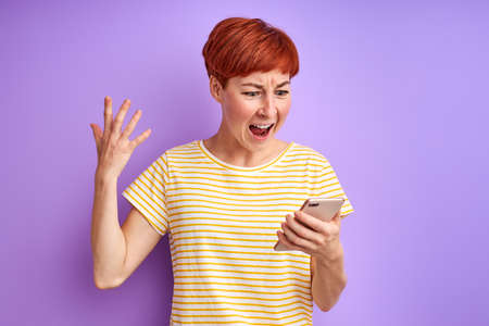 woman with short red hair scream at screen of mobile phone arguing with someone via smartphone online