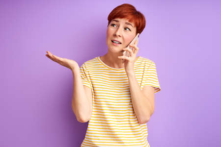 short haired female talk on phone and gesturing looking at side, discussing