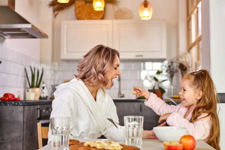 mother with kid girl eating tasty porridge for breakfast, daughter is treating mother by spoon, in light kitchen at home