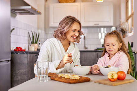 girl enjoy meal for breakfast with mom, they sit together in modern kitchen at home, wearing domestic clothes, have meal