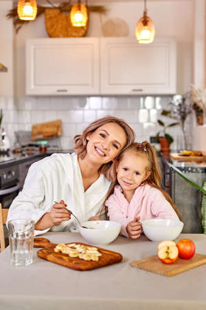 girl enjoy meal for breakfast with mom, they sit together in modern kitchen at home, wearing domestic clothes, have meal, they look at camera and smile