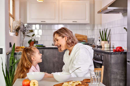 mother and child girl have fun in the kitchen while having meal, breakfast together. smile, laugh, talk, friendly mother and daughter in the morning
