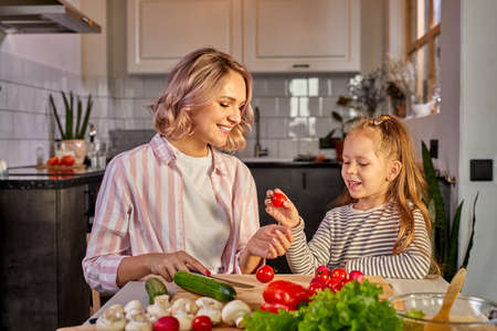 mother and kid girl preparing healthy food for family, vegan salad made from fresh vegetables, carving together Archivio Fotografico
