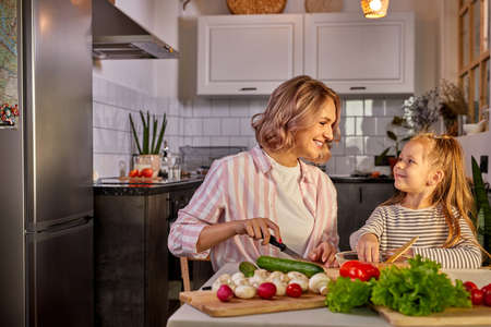 healthy food at home. happy caucasian family in the kitchen, mother and child daughter are preparing meal for dinner Archivio Fotografico