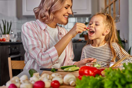 cute mom and child girl tasting fresh fruits while preparing salad for dinner, carving it together, have fun, smile. food, meal concept