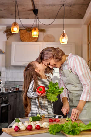 lovely mother and daughter kissing in the kitchen while cooking, preparing fresh salad from vegetables