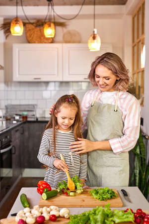 young woman teach daughter to mix salad made from fresh vegetables, in modern light kitchen