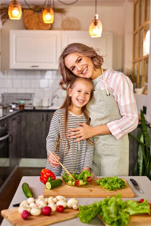 family mother with daughter cooking together, happy girl is glad to help mother preparing salad, carving fresh vegetables