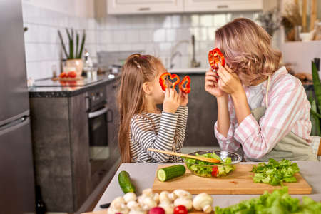 mother and daughter playing with vegetables in the kitchen while cooking, have fun Archivio Fotografico