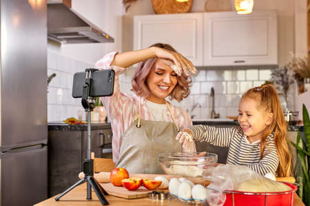 mother food blogger records the process of cooking with daughter on smartphones camera, they have fun, talk, enjoy preparing food together