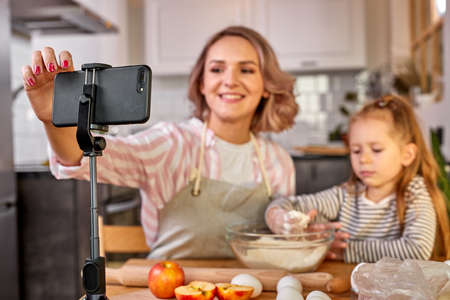 mother food blogger records the process of cooking with daughter on smartphones camera, they have fun, talk, enjoy preparing food together, focus on mobile phone